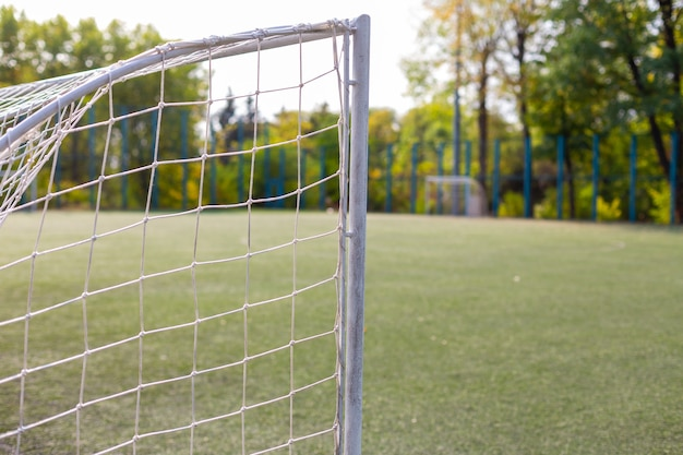 Soccer goal on empty football field at sunny day.