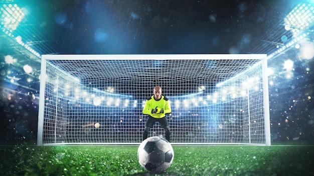 スタジアムでペナルティーキックを保存する準備ができているサッカーのゴールキーパー