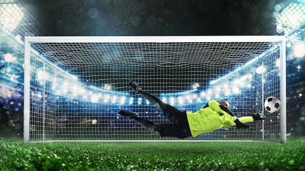 蛍光灯のユニフォームを着たサッカーのゴールキーパーは、大きなセーブを行い、試合中にゴールを回避します...