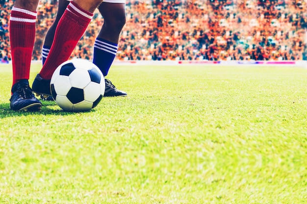 フットボールスタジアムでサッカーボールをキックするためにボールを立てたサッカーまたはフットボールの選手