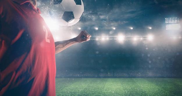 축구 선수가 경기장에서 경기하는 동안 가슴으로 공을 막습니다.