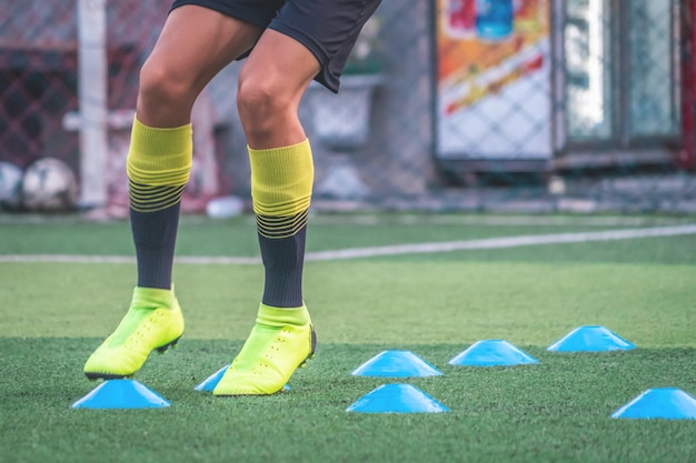Soccer player feet is training with marker in soccer academy