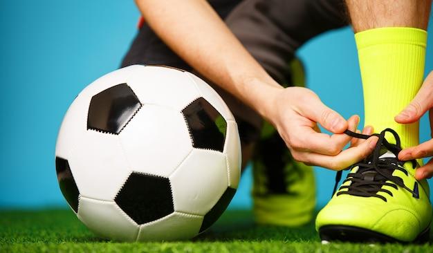 彼の靴を結ぶゲームの準備をしているサッカー選手。