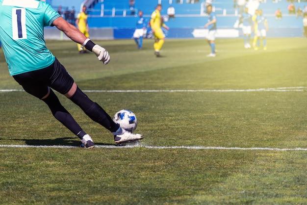 サッカー選手が自然の芝生の表面に右足でボールを打つ