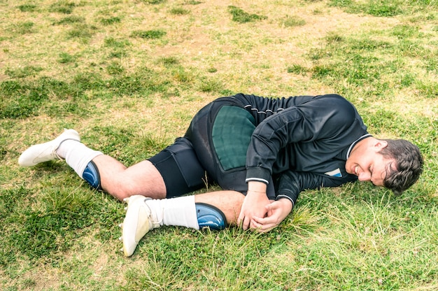 Soccer player injured during amateur football match - concept of sport failure and physical accident