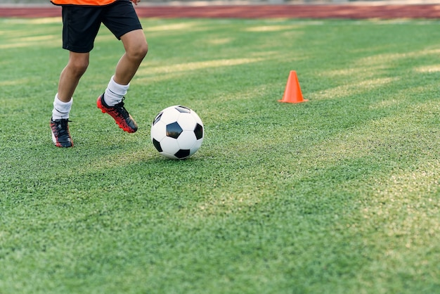 Soccer player kicking ball on field. soccer players on training session. close up footballer feet