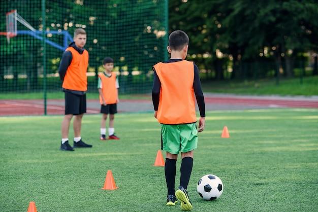 Soccer player kicking ball on field. soccer players on training session. teen footballer kicking