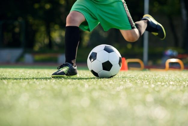Soccer player kicking ball on field.