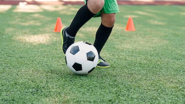Футболист ногами мяч на поле.