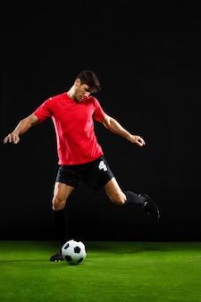 Футболист пинать мяч, играть в футбол на поле