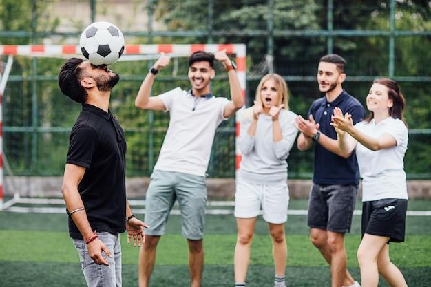 Человек футболиста играет с мячом, ударяя головой