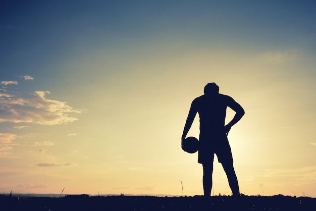 Soccer player man standing rear view in silhouette isolated on sunset background