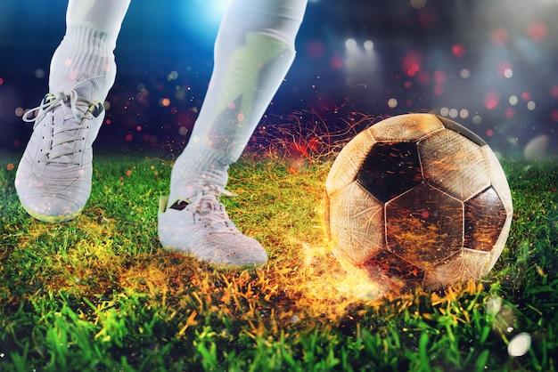 スタジアムで燃えるようなサッカーボールを蹴る準備ができているサッカー選手
