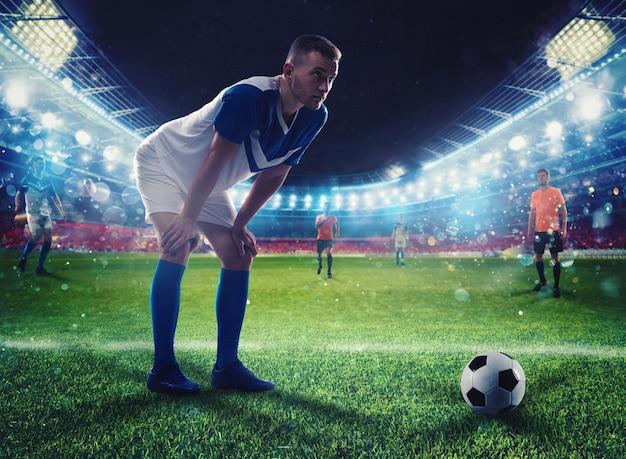 축구 선수가 경기 중 조명 경기장에서 soccerball을 걷어차 준비