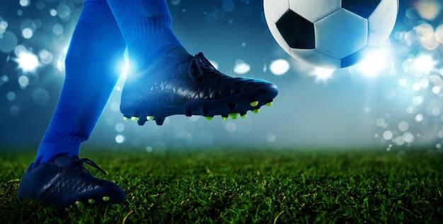 スタジアムでボールを蹴る準備ができているサッカー選手