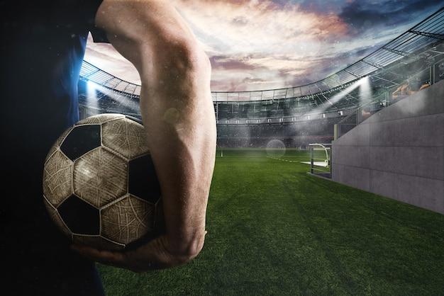 サッカー場の入り口で彼の手でボールで遊ぶ準備ができているサッカー選手