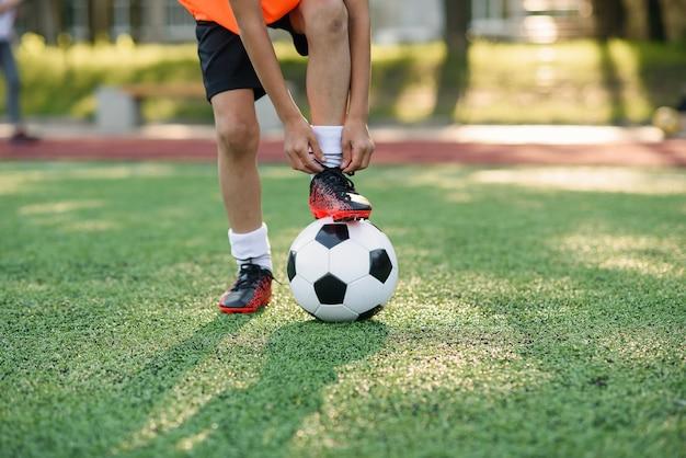 靴ひもを結ぶサッカー選手