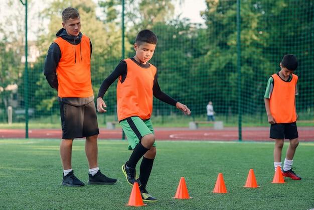 人工競技場のプラスチックオレンジコーンの間を走るサッカー選手