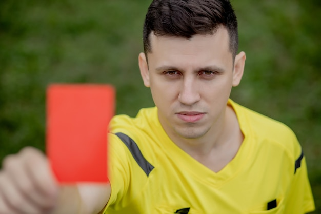 Soccer referee to point out red card to a player in the soccer stadium