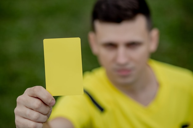 Soccer referee to point out a yellow card to a player in the soccer stadium.