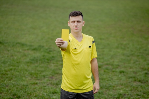 サッカー スタジアムのプレーヤーにイエロー カードを指摘するサッカーの審判。