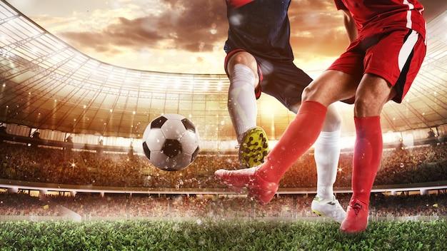 赤いユニフォームを着た選手がボールを蹴り、相手がタックルして防御するスタジアムでのサッカーシーン