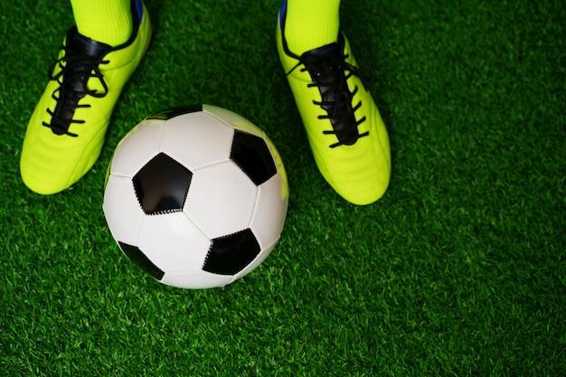 Футбольные бутсы и мяч на зеленой траве. закрыть вверх