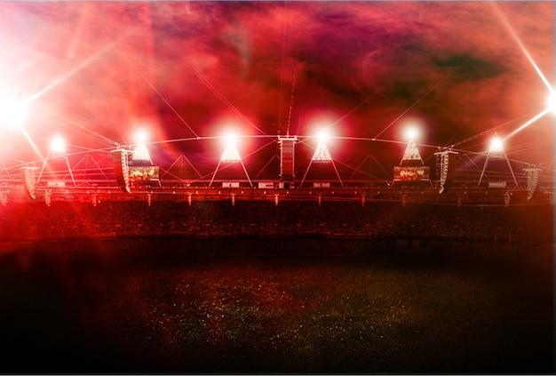 赤い蒸気の背景にサッカースタジアム
