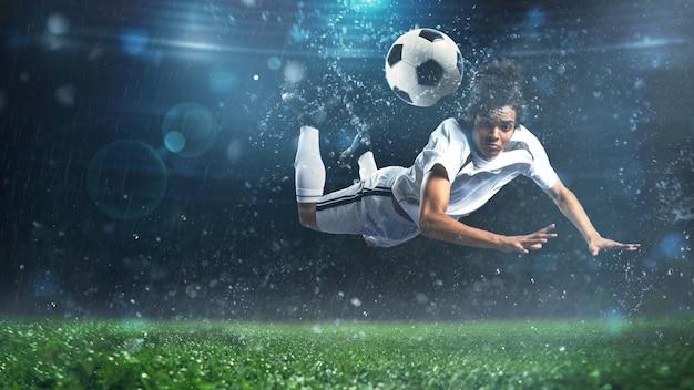 축구 스트라이커가 경기장에서 공중에서 곡예 헤드 샷으로 공을칩니다.