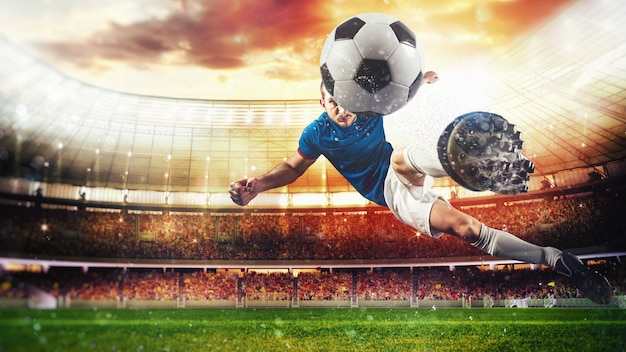 Футбольный нападающий бьет по мячу акробатическим ударом в воздухе на стадионе на закате