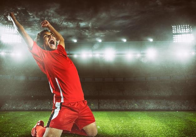 빨간 유니폼을 입은 축구 스트라이커가 경기장에서 승리를 기뻐합니다.
