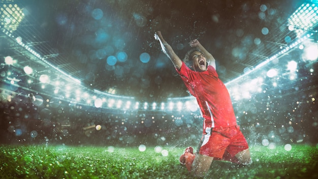 Soccer striker in red uniform rejoices for the victory at the stadium