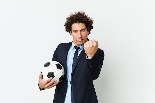 Футбольный тренер держит мяч, показывая кулак, агрессивное выражение лица.