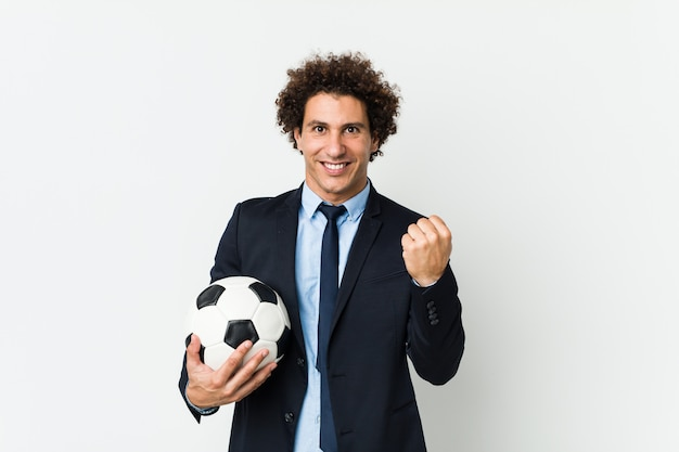 Soccer trainer holding a ball cheering carefree and excited.