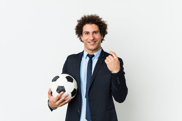 Soccer trainer holding a ball pointing with finger at you as if inviting come closer.