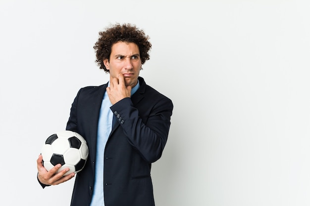 Soccer trainer holding a ball relaxed thinking about something looking at a copy space.