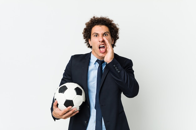 Soccer trainer holding a ball shouting excited to front.