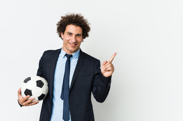 Soccer trainer holding a ball smiling cheerfully pointing with forefinger away.