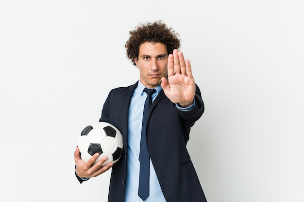 Soccer trainer holding a ball standing with outstretched hand showing stop sign, preventing you.