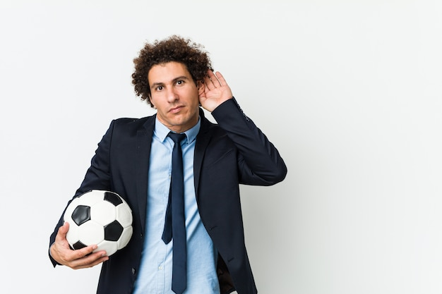 Soccer trainer holding a ball trying to listening a gossip