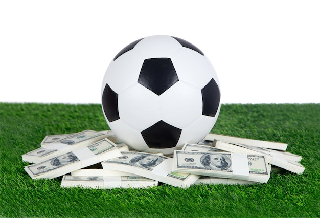 Soccer with stack of dollars on green grass