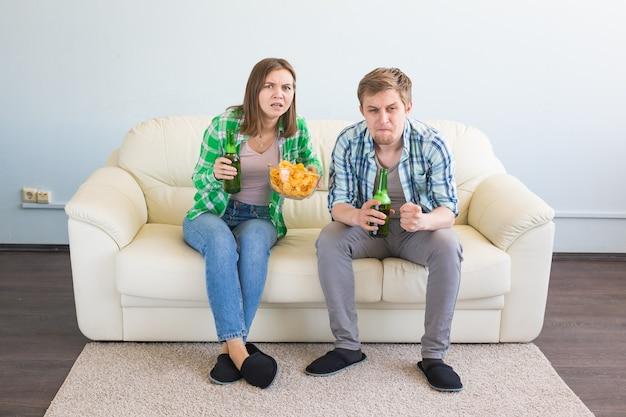 Концепция чемпионата мира по футболу - современная пара выглядит взволнованной и счастливой, смотря спортивную игру по телевизору