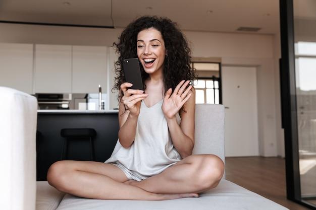 自宅のソファに足を組んで座って、ビデオ通話に携帯電話を使用しながら手を振っている社交的な愛らしい女性