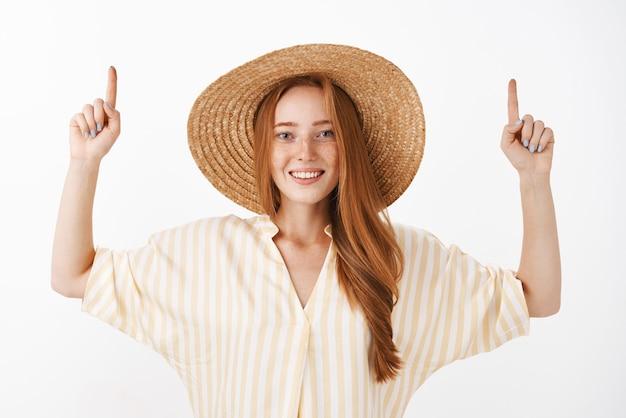 黄色のスタイリッシュなブラウスと広い笑顔で腕を上げる麦わら帽子の社交的でコミュニケーションの良いスタイリッシュな赤毛の女性