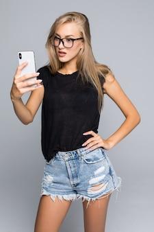 灰色の背景の上に携帯電話を使用して自分撮りまたはビデオ通話で話す社交的な美しい女性