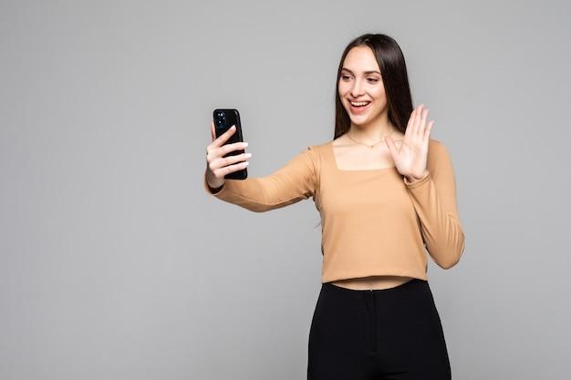 Bella donna socievole con aspetto asiatico che prende selfie o parla in videochiamata utilizzando il cellulare isolato su un muro grigio