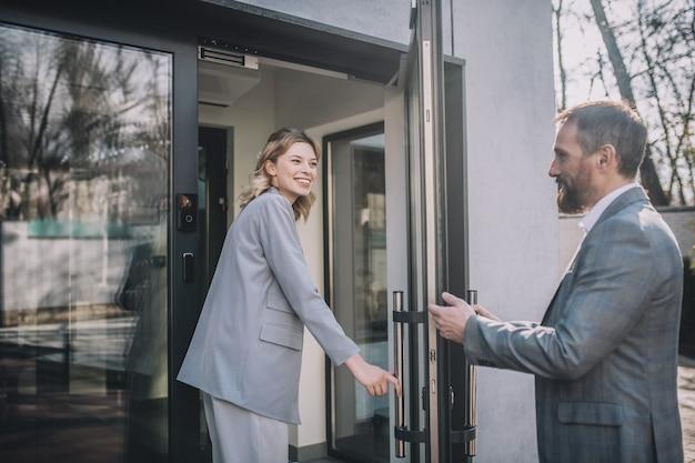 社交的な同僚。彼女のためにドアを開ける大人の幸せなビジネスマンに向かってオフィスに歩いている若いかなり笑顔の女性