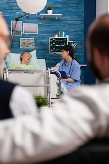 사회 보조 여성 노동자가 거실에서 아픈 노인 환자에게 약물 치료에 대해 논의합니다. 사회 서비스 간호 노인 은퇴 여성. 의료 지원