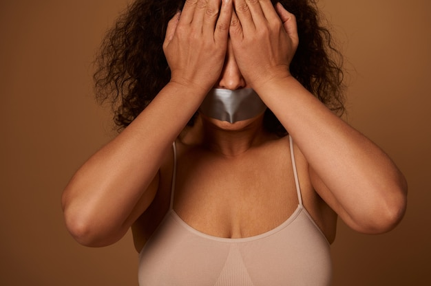Social concept for helping to fight and eliminate aggression and violence against women. scared woman with sealed mouth covering her eyes with hands, isolated on dark beige background with copy space