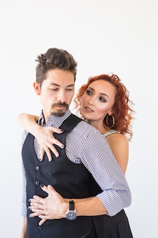 Social dance, bachata, kizomba, salsa, tango concept - woman dressed in red dress and man in a black costume over white wall.